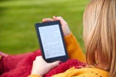 Kvinnan läser eBooken Royaltyfri Foto