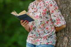 kvinnan läser en bok i staden parkerar Utbildning och lifestyl Royaltyfri Foto