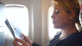 Kvinnan läser en tidskrift i en nivå bredvid ett fönster arkivfilmer