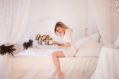 Kvinnan läser ett boksammanträde på säng Ung härlig flicka i hennes sovrum arkivbild