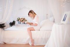 Kvinnan läser ett boksammanträde på säng Ung härlig flicka i hennes sovrum arkivbilder