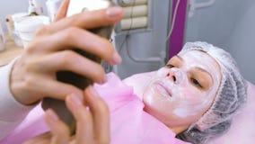 Kvinnan läser något i en mobiltelefon som ligger på tillvägagångssättet i cosmetoloist'snas kontor med en maskering på hennes fra arkivfilmer