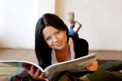 Kvinnan läser tidskriften royaltyfri fotografi