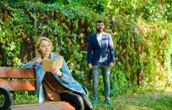 Kvinnan läste att intressera boken som sitter på, parkerar bänken intressera för bok gå för manpark Forst möte på par Vår fotografering för bildbyråer