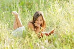 Kvinnan läste boken i parken Arkivbilder