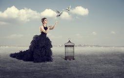 Kvinnan låter fåglarna ut arkivbild