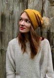 Kvinnan ler i en tröja och en hatt med en pompon fotografering för bildbyråer