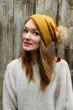 Kvinnan ler i en tröja och en hatt med en pompon royaltyfria bilder
