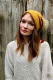 Kvinnan ler i en tröja och en hatt med en pompon royaltyfria foton
