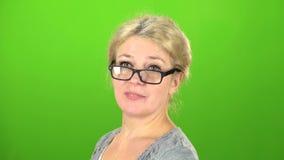 Kvinnan ler och tappar hennes exponeringsglas på ögonen grön skärm arkivfilmer