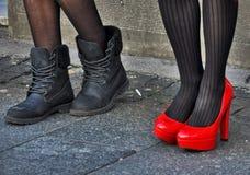 Kvinnan lägger benen på ryggen i svart, och rött skor Arkivfoton