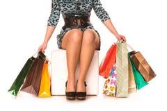 Kvinnan lägger benen på ryggen i highheels med många shopping hänger lös. Shoppingbegrepp. Royaltyfri Foto