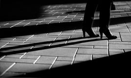 Kvinnan lägger benen på ryggen och skuggar Arkivfoton