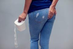 Kvinnan lider från diarré rymmer rulle för toalettpapper Magen ups royaltyfri bild