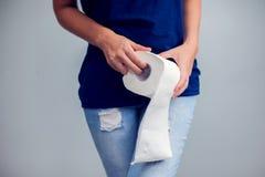 Kvinnan lider från diarré rymmer rulle för toalettpapper Magen ups royaltyfria foton