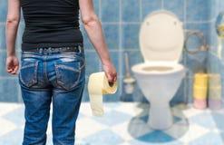 Kvinnan lider från diarré rymmer toalettpapper i hand i toalett arkivfoton