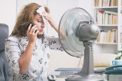 Kvinnan lider från värme i kontoret eller hemma arkivbilder