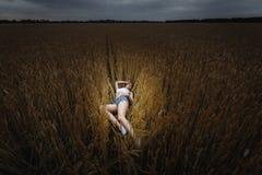 Kvinnan ligger i guld- veteåker Arkivfoto