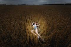 Kvinnan ligger i guld- veteåker Royaltyfri Fotografi