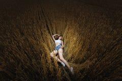 Kvinnan ligger i guld- veteåker Arkivbild
