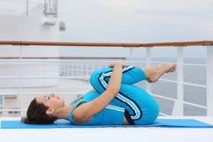 Kvinnan ligger på kryssningeyelinerdäck och övar royaltyfri fotografi