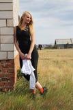 Kvinnan lutar på hustegelstenväggen. Royaltyfri Bild