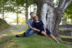 Kvinnan lutar tillbaka mot make under träd Royaltyfri Bild