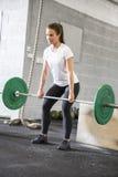Kvinnan lyfter deadlift på konditionidrottshallen Arkivbild