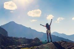 Kvinnan lyftte henne händer upp i bergen arkivfoton