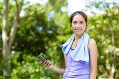 Kvinnan lyssnar till musik med mobiltelefonen Royaltyfria Foton
