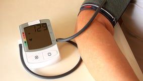 Kvinnan mäter blodtryck med instrumentet av mätningen arkivfilmer