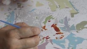 Kvinnan målar akrylmålarfärger som målar vid nummer, den antistress hobbyen video 1080p lager videofilmer