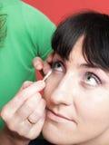Kvinnan målar framsidan med makeup Arkivbilder