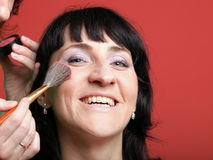 Kvinnan målar framsidan med makeup Arkivfoton