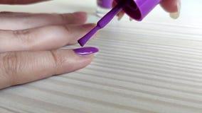 Kvinnan målar spikar med lilor spikar polermedel stock video