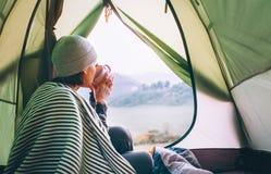 Kvinnan möter den kalla morgonen som sitter i touristic tält med koppen av varmt te Aktiv semesterbegreppsbild royaltyfri fotografi
