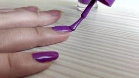 Kvinnan m?lar spikar med lilor spikar polermedel stock video