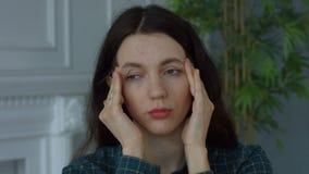 Kvinnan masserar tempel för att avlösa huvudvärk hemma lager videofilmer