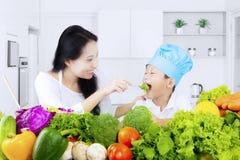 Kvinnan matar hans son med sallad Arkivfoto