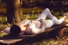 Kvinnan med ögon stängde att koppla av på en bänk i natur Royaltyfri Bild