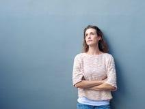 Kvinnan med armar korsade att se bort med fundersamt uttryck royaltyfria bilder