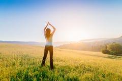 Kvinnan med armar lyftte upp till himmel som firar ny dag Royaltyfri Foto