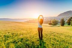 Kvinnan med armar lyftte upp till himmel som firar ny dag Fotografering för Bildbyråer