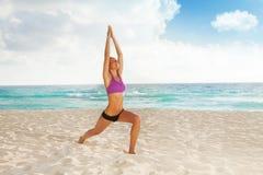 Kvinnan med armar up och ben som gör ifrån varandra yoga Royaltyfri Bild