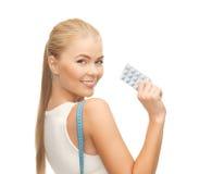 Kvinnan med att mäta bandet och bantar preventivpillerar Arkivfoto