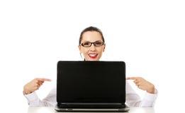 Kvinnan med bärbar dator pekar till avskärma arkivfoton