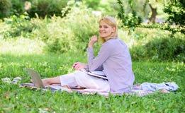 Kvinnan med bärbara datorn sitter gräsängen Bästa jobb att arbeta avlägset Frilans- arbete för affärsdam utomhus Avlägset jobb royaltyfri bild