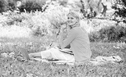 Kvinnan med bärbara datorn sitter gräsängen Bästa jobb att arbeta avlägset Frilans- arbete för affärsdam utomhus Avlägset jobb arkivbild