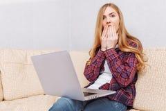 Kvinnan med bärbara datorn sitter på den förvånade soffan och blickar arkivbilder
