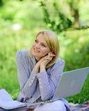 Kvinnan med bärbara datorn sitter på filtgräsäng Online-frilans- karriärbegrepp Angenäm ockupation Starta för handbok arkivbild